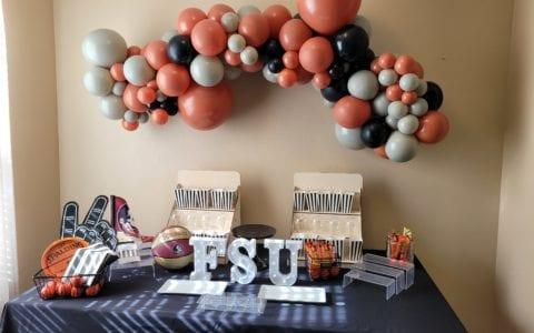 Organic Balloon Display over cake table with black burnt orange stone grey