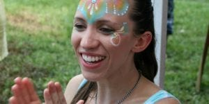 Photo of a happy mom clapping for the entertainer and wearing face paint at a birthday party