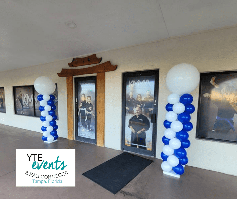 A pair of white and blue balloon columns, one of each side of the entrance to a martial arts school.