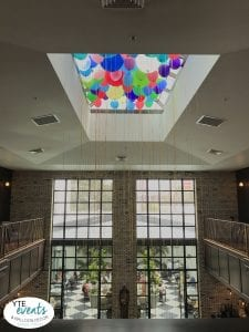 When The Oxford Exchange wanted to do something special for their 5th anniversary celebration, they reached out to YTE Events & Decor to create something special to commemorate the event. While we did a big balloon installation on the outside of the building, we felt the customers inside may want to look at something pretty and colorful as well. We decided to go with something simple as to not distract from the elegant atmosphere inside. We decided to fill the skylight with balloons in the same colors that were used outside. To make it stand out even more, we used balloons in all sizes to create a feel of texture and movement. Strings were kept on the balloons to add to the feel of a birthday party as well as for easy take down. The sunlight changes throughout the day made for an interesting and beautiful kaleidoscope of colors that many of the customers in the café area loved. This project was so much fun to work on and we are so excited The Oxford Exchange reached out to YTE Events and Balloon Decor to create something special for their anniversary.