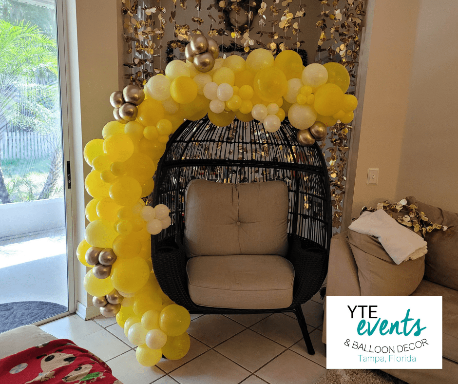 Baby shower balloon decor for private residence made with yellow and gold balloons in a crescent shape.