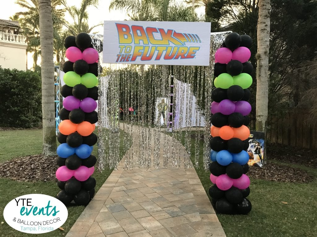 Back to the future themed entrance with silver tassels and neon columns of balloons