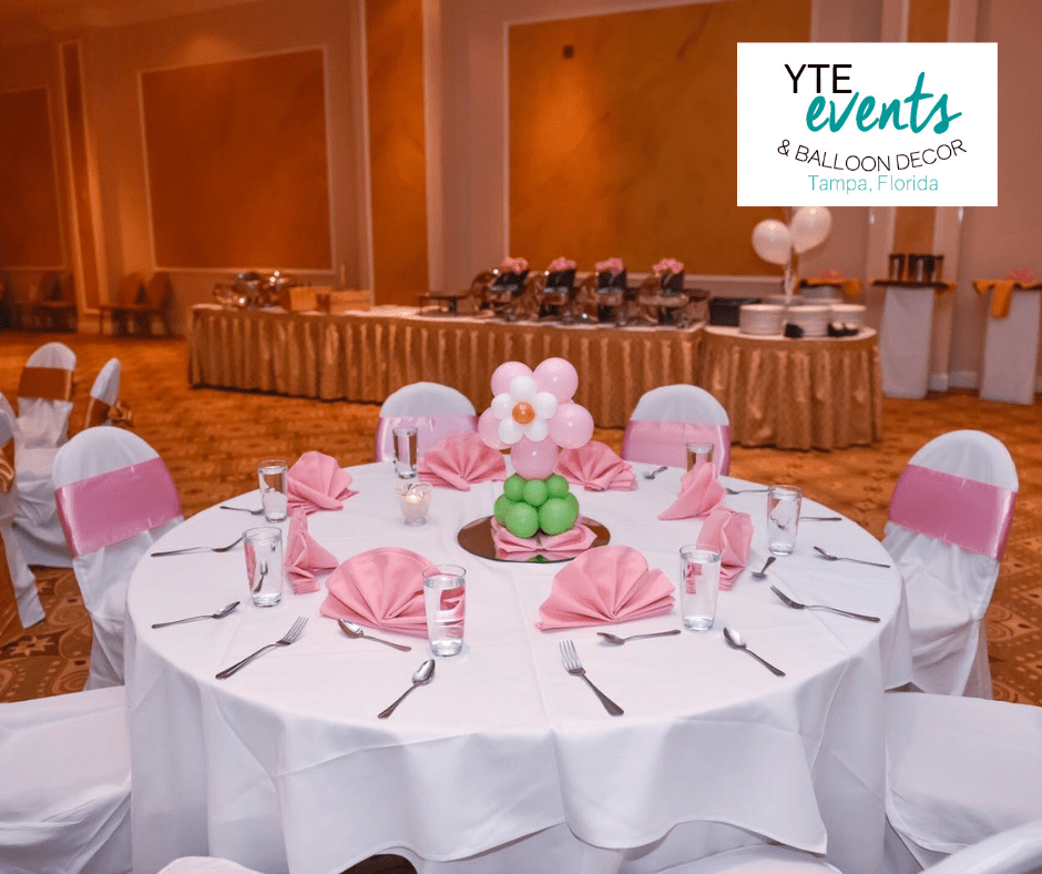 Balloon centerpiece of a pink and white flower with a green stem in a banquet hall .