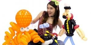 Young girl holds a plethora of balloon figures including an octopus, snail, ladybug, whale, bunny ears, and popeye made out of balloons