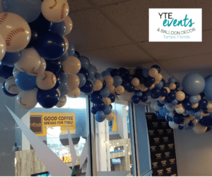 Blue and white balloon ceiling decor where the white balloons are baseball-patterned.
