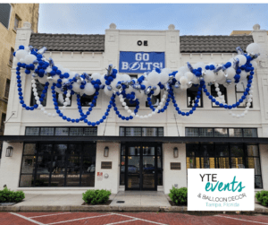 Blue and white organic balloon decor hung above the awning of the Oxford Exchange with strings of blue and white balloons hanging down from the main decor piece.