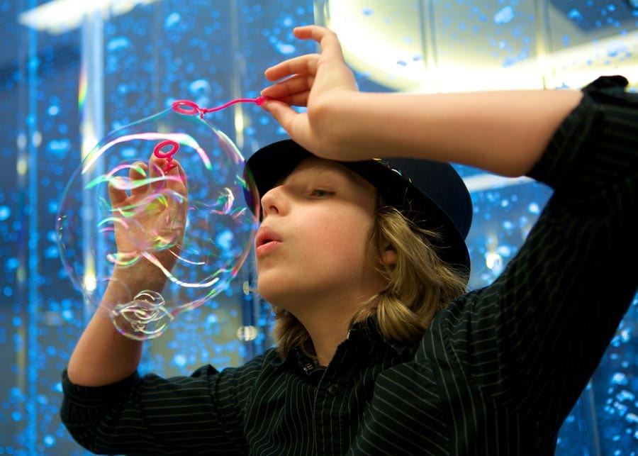 Blaise blows up a bubble in front of blue backdrop