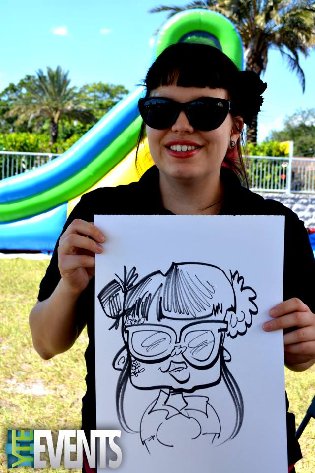 girl holds a black and white caricature art rendering of herself outside at sunny event
