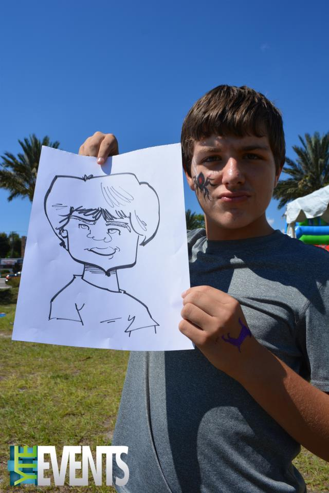 boy holds his custom caricature art drawing in front of him