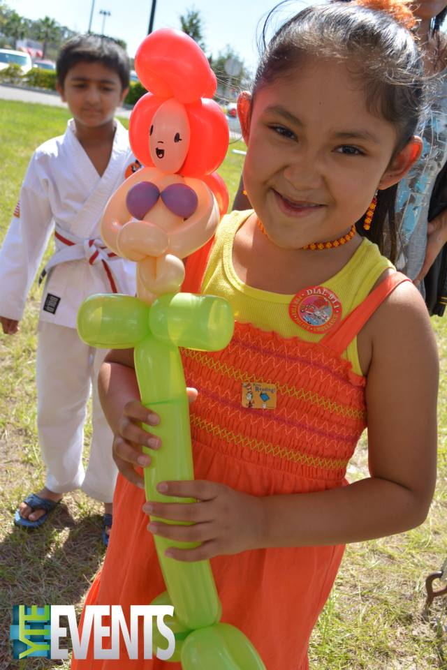 small girl holding a balloon figure of the little mermaid