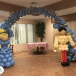 Cinderella sculpture and prince charming sculpture for baby shower in front of arch organic tapered decorations over cake table