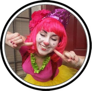 Clown in colorful outfit smiling at the camera