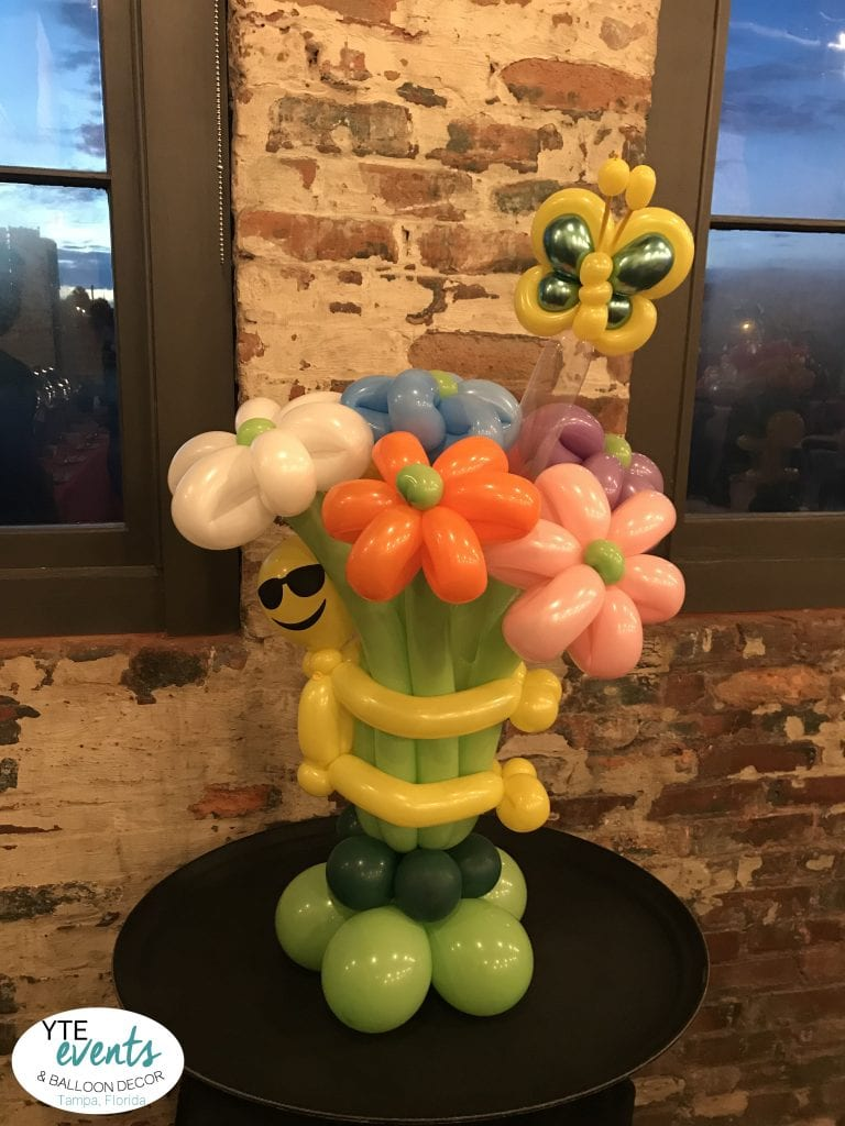 Cool Emoji Smiley Face balloon sculpture bouquet with flowers and butterfly for corporate event in Tampa florida at Armature Works