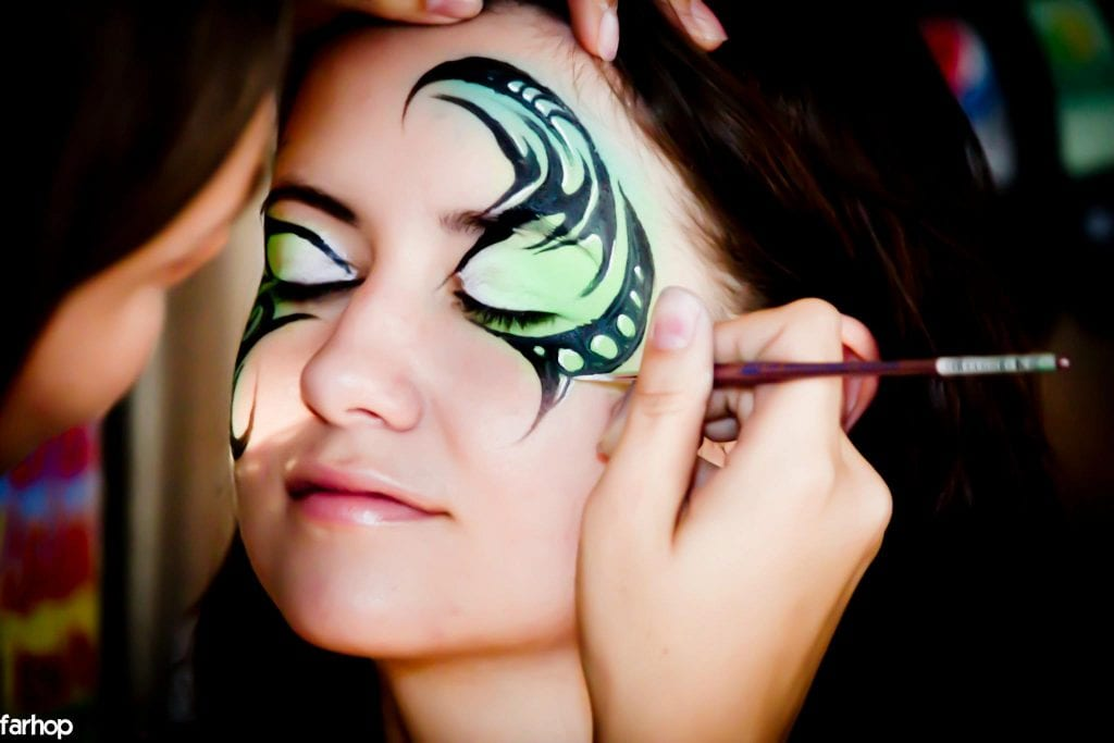 neon reactive face paints being applies to an adult face for an event