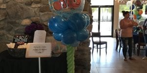 """We found Nemo! YTE Events & Balloon Decor loves Disney. We get asked a lot to do something Disney oriented to make this Finding Nemo themed baby shower extra special and fun for not only children, but also adults who have """"Disney fever"""". For this event at a local restaurant, decorations needed to be easy to move, take down, and not damage the inside. Our balloon twisters decided on a column in ocean blue colors. The marble blues of the bigger balloons gave it a feel of moving ocean currents. The smaller, light blue balloons gave a feel of bubbles. The stem was a light green twisting to the top where Nemo sat. Nemo was definitely the star of the show and having a clear balloon made it seem he was swimming at the top of the column. Balloon columns are a great way to add decoration to any event, but especially at events where decorations are limited to rules and regulations, such as restaurants, cafés, or reception halls. Cartoon character toppers can be customized to fit your event including superheroes, princesses, other Disney characters, or just simple colors. Book YTE Events & Balloon Decor and any location can be made into a fun and inviting place for your guests and event!"""