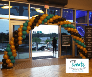 Green, yellow, and black balloon archway for the entrance to the TopGolf lobby.