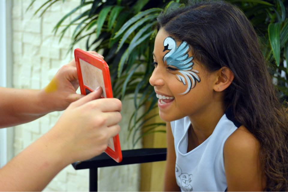 Girl smiling into a mirror as she looks at her freshly painted swan face paint