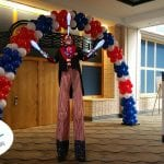 Juggler on stilts in front of patriotic archway in tampa convention center