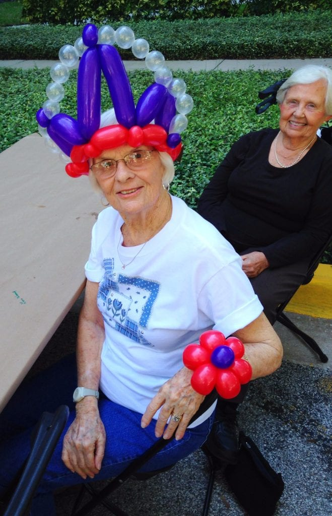 Balloon figures on guests at a retirement home. Includes princess crowns and flower bracelets