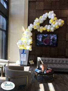 Movie theatre lobbies are often plastered with up coming movie posters or cut outs, but for one local movie theatre, they wanted something that POPPED! out at guests as they came into the lobby for a luxury movie viewing experience. In addition they were running a campaign and wanted something that promoted it and draw in attention of their guests. YTE Events & Balloon Decor decided to create a fun and whimsical centerpiece that featured everyone's favorite movie snack: popcorn! Our artists created a balloon sculpture using their cardboard popcorn bucket. We filled it with yellow and white balloons and built up the sculpture onto the adjoining wall to make it appear that popcorn was overflowing out of the bucket. Balloon kernels were also made out of balloons and placed on the floor to give it a realistic feel. Balloon displays are a great way to promote a business event or promotion. Sales, special events, grand openings, or even customer appreciations are all events that could benefit from a balloon display. Our artists can incorporate pre-made displays and turn them into something extraordinary with the addition of a few colorful balloons. Whether you have a large movie theatre or a small store front, YTE Events & Balloon Decor can help you turn your event into something customer wont forget.