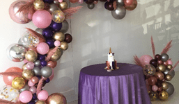 No matter how you look at it, organic balloon garland backdrops are hot right now! These elegant balloon installations look great on everything from a printed backdrop, or step and repeat, to a faux boxwood hedge wall, or pallet wall. Best of all, a balloon garland's design is infinitely customizable. Here are a few inspired ways to make this trend your own. Frame Your Logo Organic balloon garlands usually frame a backdrop. But you don't have to follow the pack! This client wanted to ensure that its logo was the focus of the backdrop and that the beautiful balloons would appear prominently in each photo. Incorporate Flowers and Greenery A garland's design itself can also highlight a company's name, brand or message more subtly. This balloon installation, for example, has olive branch greenery to celebrate an anniversary of a company with the same name. Red confetti balloons add a pop of color! Here, a summery yellow organic balloon garland softened with fresh greenery elevates this simple pallet wall into breathtaking backdrop. Floral additions to balloon garlands can range from the addition of greenery (like the olive branches), to flowers that match a bride's bouquet, to custom accents. The organic garland for this upscale unicorn-themed birthday party, for example, included hand-dyed pampas grass! Color Blocking Color blocking, or layering sections of a single color, is another popular approach to organic balloon garland design. Here, the rainbow color blocking here coordinated with the client's event props and decor. Another color-blocked organic installation shows the possibilities for this type of design. This balloon photo frame was the highlight of a baby shower. Guests' photos lit up social media during and after the event! Add Some Shine If you love glitter and your event demands glitz, consider a balloon garland created from a mix of professional Chrome latex and foil Orbz. Larger balloons add drama and visual impact For other events, consider tiny pops o