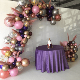 "No matter how you look at it, organic balloon garland backdrops are hot right now! These elegant balloon installations look great on everything from a printed backdrop, or step and repeat, to a faux boxwood hedge wall, or pallet wall. Best of all, a balloon garland's design is infinitely customizable. Here are a few inspired ways to make this trend your own. Frame Your Logo Organic balloon garlands usually frame a backdrop. But you don't have to follow the pack! This client wanted to ensure that its logo was the focus of the backdrop and that the beautiful balloons would appear prominently in each photo. Incorporate Flowers and Greenery A garland's design itself can also highlight a company's name, brand or message more subtly. This balloon installation, for example, has olive branch greenery to celebrate an anniversary of a company with the same name. Red confetti balloons add a pop of color! Here, a summery yellow organic balloon garland softened with fresh greenery elevates this simple pallet wall into breathtaking backdrop. Floral additions to balloon garlands can range from the addition of greenery (like the olive branches), to flowers that match a bride's bouquet, to custom accents. The organic garland for this upscale unicorn-themed birthday party, for example, included hand-dyed pampas grass! Color Blocking Color blocking, or layering sections of a single color, is another popular approach to organic balloon garland design. Here, the rainbow color blocking here coordinated with the client's event props and decor. Another color-blocked organic installation shows the possibilities for this type of design. This balloon photo frame was the highlight of a baby shower. Guests' photos lit up social media during and after the event! Add Some Shine If you love glitter and your event demands glitz, consider a balloon garland created from a mix of professional Chrome latex and foil Orbz. Larger balloons add drama and visual impact For other events, consider tiny pops of shine. Mylar accent balloons, like the mylar ""5"" that anchors this balloon garland, provide visual texture, as does the iridescent metallic fringe hanging behind it. Inspired? Contact us today to order an organic balloon garland installation for your event!"