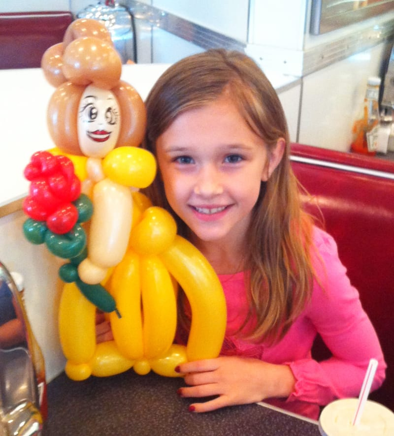 Girl in restaurant holding a balloon animal of belle from beauty and the beast