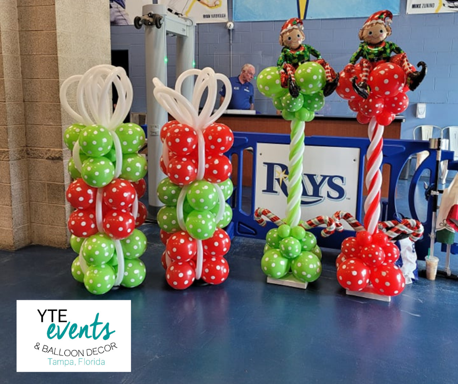 Red and green balloon columns that look like stacks of Christmas presents and topped with monkey elves made out of foil balloons.