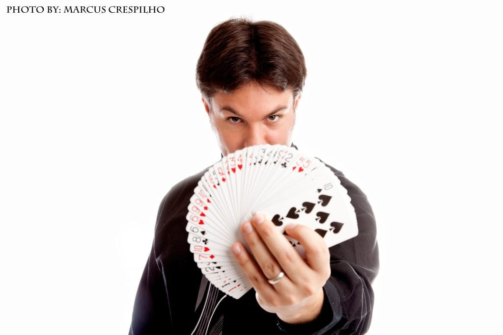 magician holding a fan of cards in front of him