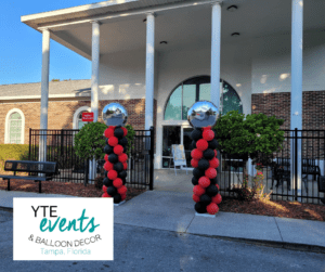 Tampa day school graduation with red and black spiral columns and foil toppers.