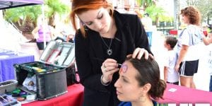 shows a face painter painting a guest with face paint supplies in the background of an event booth