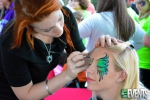 face painter paints a green butterfly on a guests face at a festival