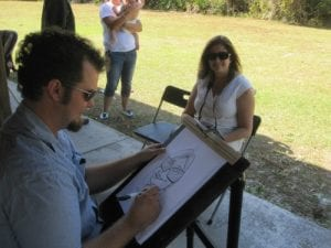 caricature artist drawing a caricature of a lady in front of him at an event outside