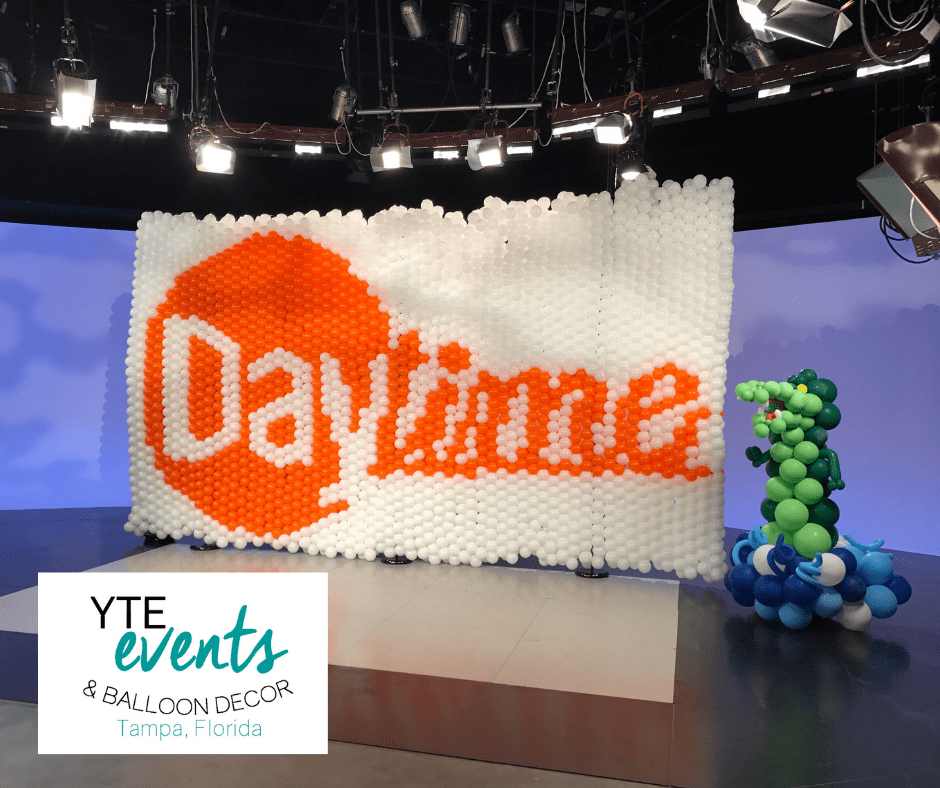 White and orange balloon wall and alligator balloon sculpture for Daytime.