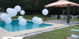 White balloons strung at various heights in a pool next to a pavilion at an event.