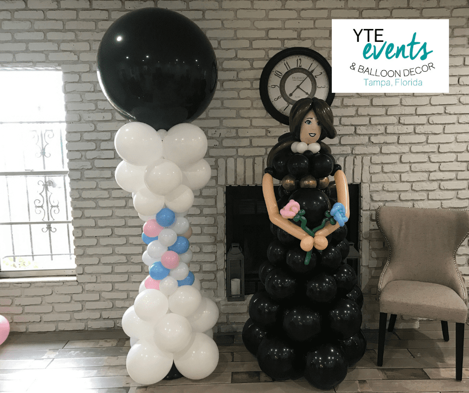 White, pink and blue balloon column with a black balloon topper adjacent to a balloon sculpture of a woman in a black dress with blue and pink flowers.