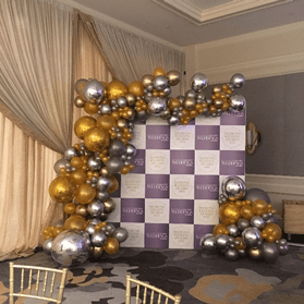 gold and silver balloon garland organic on checkered backdrop for special event